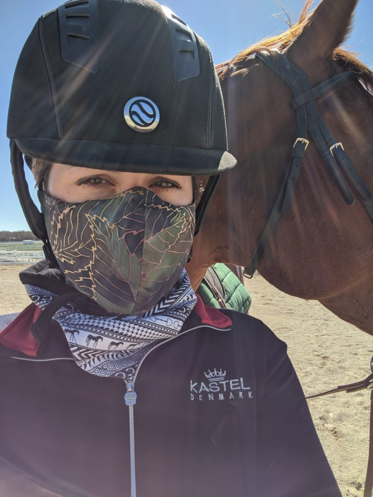 person in foreground wearing riding helmet and a face mask, black and white scarf, dark blue shirt. Red horse in background.